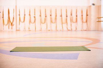 Empty space in fitness center, brick wall, natural wooden floor, modern loft studio, unrolled yoga mat on the floor.