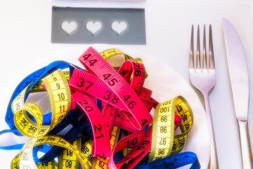 scale and plate of tape with cutlery. diet and slimming concept
