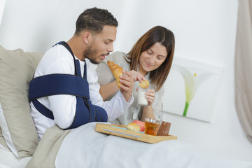 young couple eating the breakfast on the bed