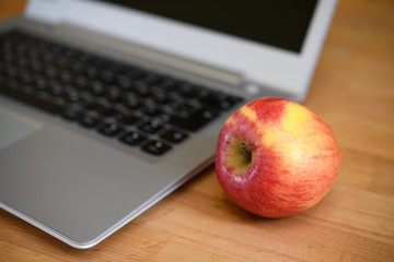 laptop with apple on wooden ground