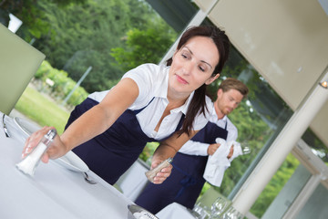 smiling waitress setting the table in a restaurant