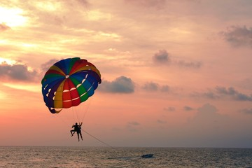 Silhouette of two people on parachute against the sunset sky