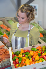 joyful smiling female worker choosing fruits in food shop