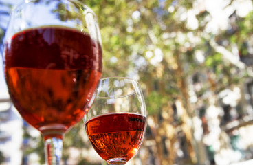 two glasses of red wine on the table of a street cafe on a bright sunny day