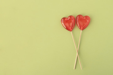 Two Lollipops in heart shape on green background