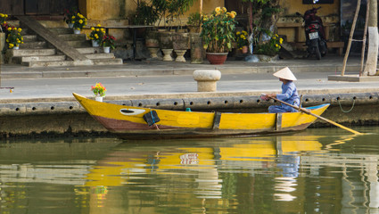 woman wearing iconic conical straw hat moving  her yellow wooden boat with oar  along river in old town of Hoi An, Vietnam
