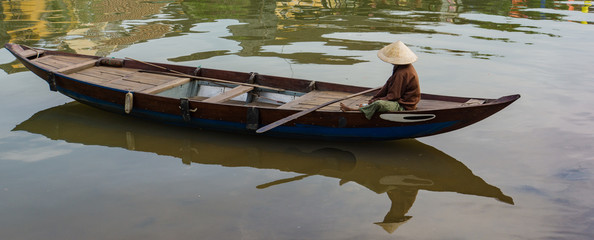 woman wearing iconic conical straw hat resting on her  wooden boat with oar  along river in old town of Hoi An, Vietnam