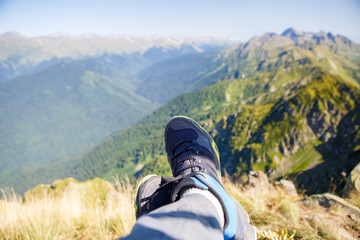 Photo of man in sneakers and picturesque mountainous landscape