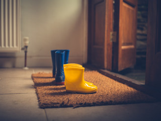 Two pairs of rubber boots by door
