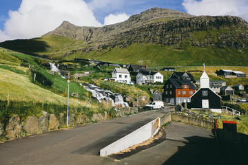 Beautiful old scandinavian village in Faroe Islands, boat, church, cliffs