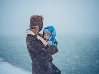 Mother by the water with toddler in the snow