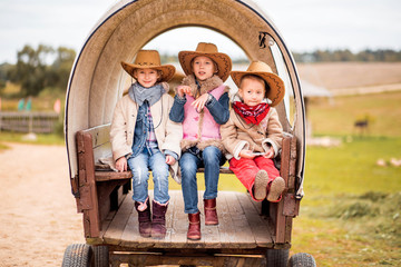 three sisters have fun on the farm near the old cart