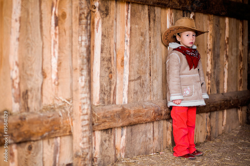 a little girl in a cowboy hat stands near the wall of a barn