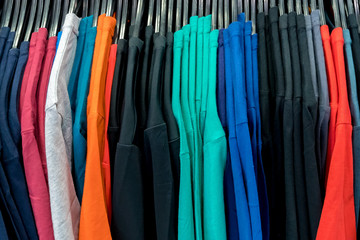 Colorful t-shirt for the man on hangers in store, background