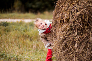 a little cheerful girl next to a haystack