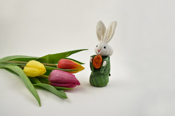 Easter Bunny with tulips stock images. Easter decoration on a white background. Spring decoration images. Bouquet of colorful tulips