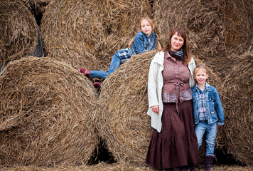 family - mother and two daughters are resting near the hay