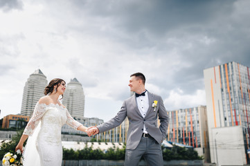 The newlyweds go holding hands, against the background of the city and high buildings, towers and thick clouds. The bridegroom leads the bride and smiles.