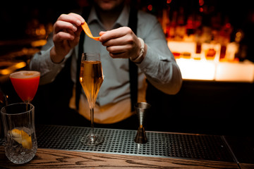 Bartender serving delicious champagne cocktail in night club