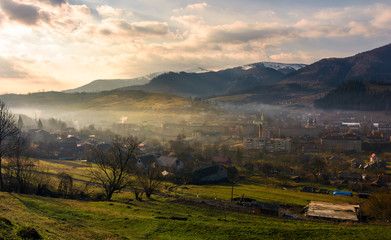 cloudy and foggy sunrise in Carpathian mountains. Small town Volovets in the valley at the foot of Borzhava mountain ridge with snowy tops. lovely springtime scenery