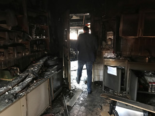 A man walks inside a mosque after it was destroyed by a fire in Berlin