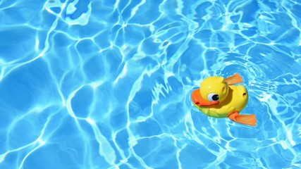 Yellow rubber duck on the water in hot sunny day. Summer background for traveling and vacation. Holiday idyllic.