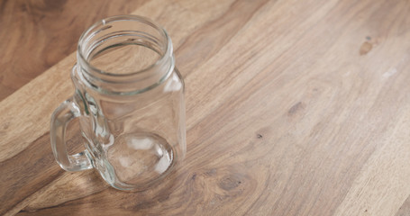 glass jar with handle on wood table