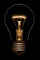 Photo of silhouette of incandescent filament bulbs on a black background. Detail of a lit European bulb. Product photo flashbulb.