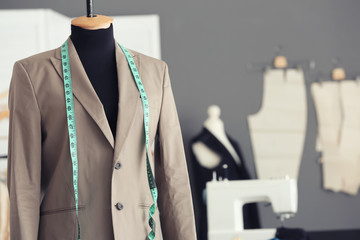 Tailor's mannequin with formal jacket and measuring tape in atelier