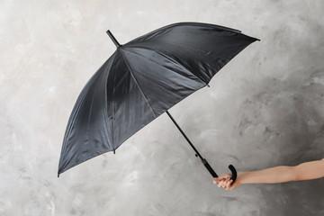 Woman holding black umbrella on grey background