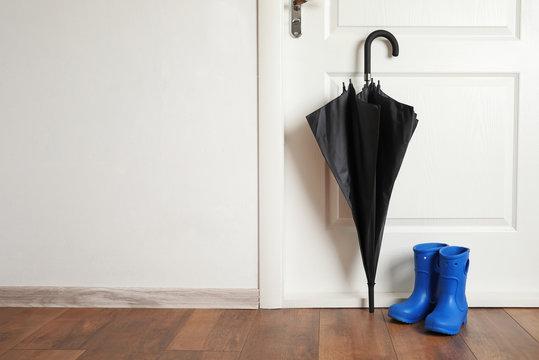 Black umbrella and gumboots on floor near door