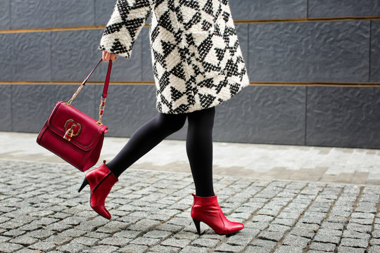 Stylish woman in red shoes walking down the street