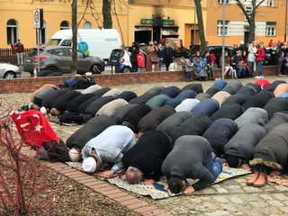 People pray near a mosque after it was destroyed by a fire in Berlin