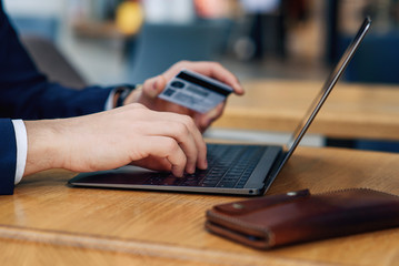 Male hand holding credit card typing numbers on computer while sitting at cafe, selective focus. Web banking and international network payment. Online shopping, credit card payment concept.