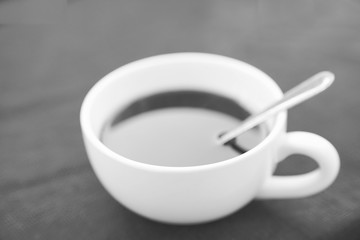 White cup of black coffee on black background in black and white