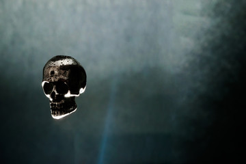 Metal Skull Levitating in Air on Black Background Illuminated by Light