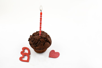 Romatic muffin with candle stock images. Chocolate muffin with hearts on a white background. Sweet party pastry. Valentines Day concept