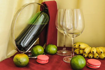 a bottle of wine glasses and fruit