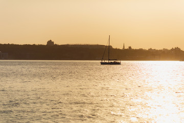 Beautiful seascape. Lonely boat with sails in a calm sea with reflection of sunlight near a industrial seaport on the coastline against the background of a clear warm evening sunset