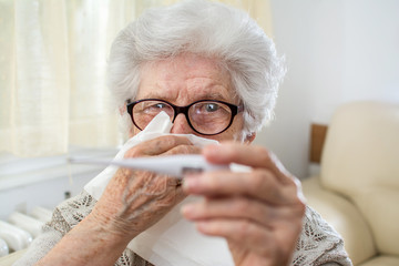 Close up portrait of sick senior woman checking body temperature with thermometer and holding a tissue paper over her face.