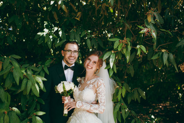 Beautiful wedding photosession. Groom in black suit, white shirt, bow tie and glasses and bride in elegant lace dress with veil and bouquet of white and pink flowers amidst the branches of green bush