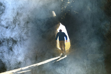 entrance to the cave, a male traveler stands in the rays of light at the exit of the cave, historical ruins, the concept of treasure search