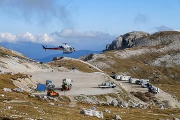 Hubschrauber in den Bergen holt flüssigen Beton für Bauarbeiten auf einer schwer zugänglichen Hütte
