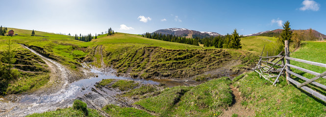 panorama of mountainous rural countryside. spruce forest on grassy slopes. wooden fence near the brook. mountain ridge with snowy tops in the distance