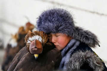 A young hunter rests next to his a tamed golden eagle during an annual hunters competition at Almaty hippodrome