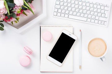 Lady bloggers work desk with pink flowers and macaron cakes on w