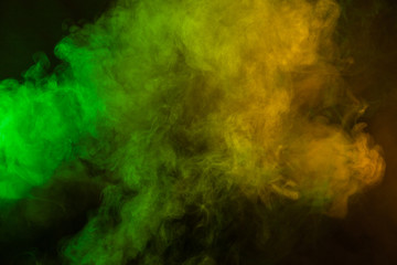 Green and yellow smoke in dark background. Texture and desktop picture