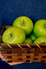Green apples in a wicker basket in woman's hands