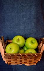 Green apples in a wicker basket in woman's hands. Copy space
