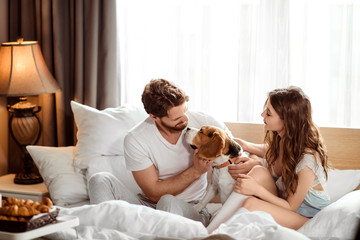 Positive female and male have fun together with their dog in bed, enjoy calm domestic atmosphere and togetherness. Family couple plays with favourite dog in bedroom. True friendship and devotion